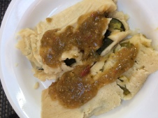 A green chili and cheese tamale and a zucchini and mushroom tamale with Gilly Loco Salsa